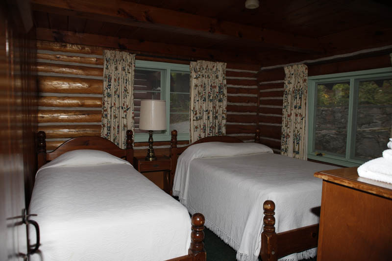 log cabin room with two twin beds