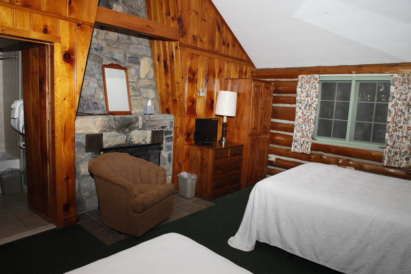 Adirondack Log Cabin room with large stone fireplace
