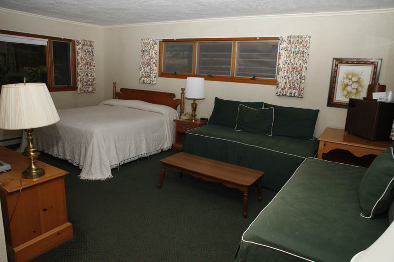 Redwood Cottages room with green couches and bed