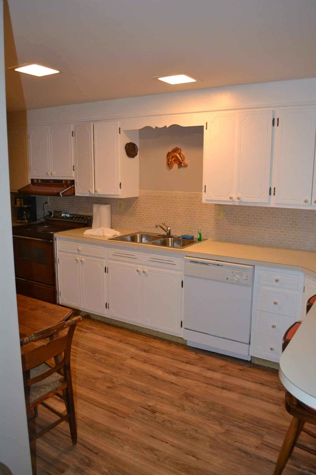 White cabinets in kitchen with wood flooring